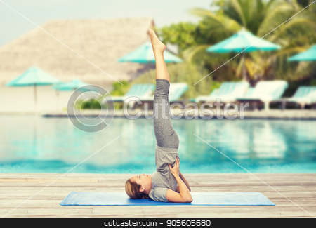 woman making yoga in shoulderstand pose on mat stock photo, fitness, sport, people and healthy lifestyle concept - woman making yoga in shoulderstand pose on mat over beach and swimming pool background by Syda Productions
