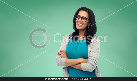 happy smiling young indian woman in glasses stock photo, education, school and people concept - happy smiling young indian student woman or teacher in glasses over green chalkboard background by Syda Productions