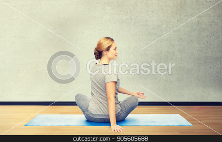 woman making yoga in twist pose on mat stock photo, fitness, sport, people and healthy lifestyle concept - woman making yoga in twist pose on mat over gym room background by Syda Productions