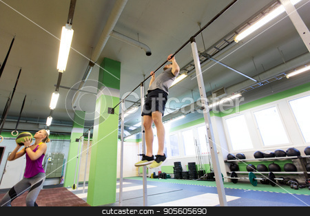 woman and man exercising in gym stock photo, fitness, sport and training concept - woman and man with medicine ball and horizontal bar exercising in gym by Syda Productions