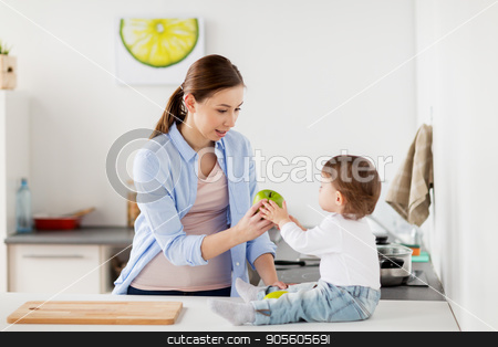 mother giving green apple to baby at home kitchen stock photo, family, food, healthy eating, people and motherhood concept - happy young mother giving green apple to baby at home kitchen by Syda Productions