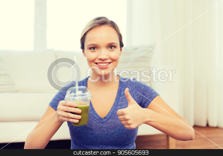 happy woman with cup of smoothie showing thumbs up stock photo, people, diet  and healthy lifestyle concept - happy woman with cup of smoothie at home and showing thumbs up by Syda Productions