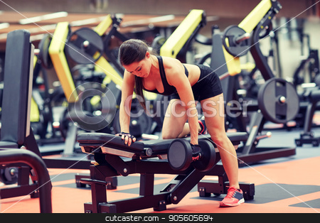young woman flexing muscles with dumbbell in gym stock photo, sport, fitness, bodybuilding, weightlifting and people concept - young woman with dumbbell flexing muscles in gym from back by Syda Productions