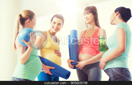 group of happy pregnant women talking in gym stock photo, pregnancy, sport, fitness, people and healthy lifestyle concept - group of happy pregnant women with sports equipment talking in gym by Syda Productions