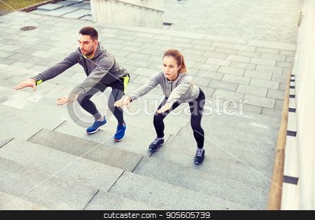 couple doing squats on city street stairs stock photo, fitness, sport, people, exercising and lifestyle concept - couple doing squats on city street stairs by Syda Productions