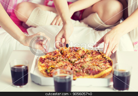 friends or teen girls eating pizza at home stock photo, friendship, people, pajama party and junk food concept - close up of friends or teenage girls eating pizza at home by Syda Productions