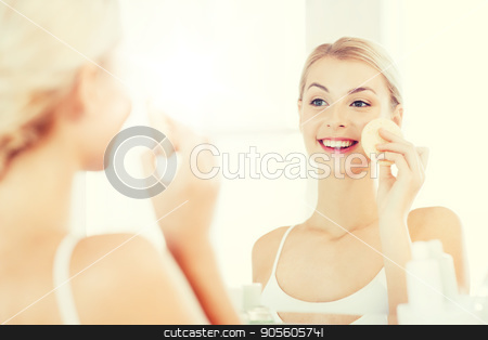 young woman washing face with sponge at bathroom stock photo, beauty, skin care and people concept - smiling young woman washing her face with facial cleansing sponge at bathroom by Syda Productions