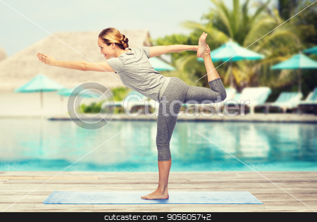 woman making yoga in lord of the dance pose on mat stock photo, fitness, sport, people and healthy lifestyle concept - woman making yoga in lord of the dance pose on mat over beach and swimming pool background by Syda Productions