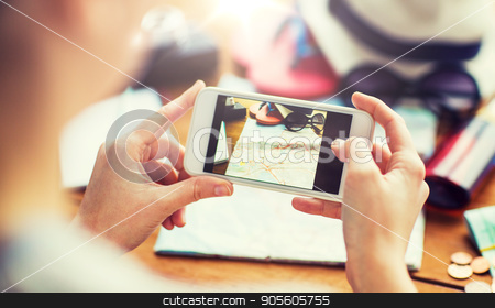 close up of woman with smartphone and travel stuff stock photo, vacation, tourism, travel, technology and people concept - close up of woman with smartphone photographing map and travel stuff by Syda Productions