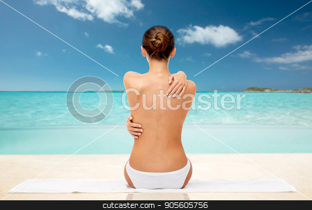 beautiful topless woman with towel on summer beach stock photo, beauty, people and bodycare concept - beautiful topless young woman in white panties sitting on towel from back over exotic tropical beach background by Syda Productions