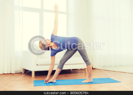 woman making yoga triangle pose on mat stock photo, fitness, sport, people and healthy lifestyle concept - woman making yoga triangle pose on mat by Syda Productions