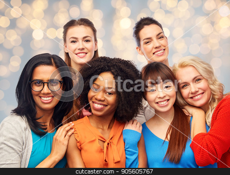 international group of happy women hugging stock photo, diversity, ethnicity and people concept - international group of happy smiling different women hugging over holidays lights background by Syda Productions