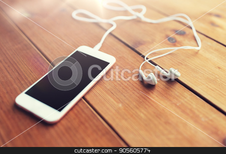 close up of blank smartphone and earphones on wood stock photo, technology, music, gadget and object concept - close up of white smartphone and earphones on wooden surface with copy space by Syda Productions