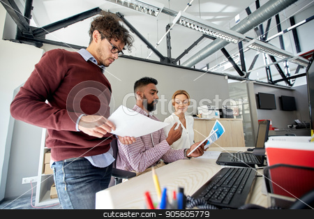 business team with tablet pc and papers in office stock photo, business, technology and people concept - international creative team with papers and tablet pc computer and papers in office by Syda Productions