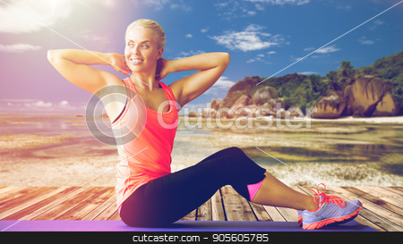 smiling woman exercising on mat outdoors stock photo, fitness, sport, training and people concept - smiling woman exercising on mat outdoors over exotic tropical beach background by Syda Productions