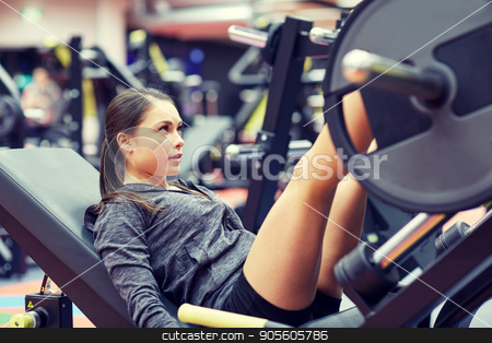 woman flexing muscles on leg press machine in gym stock photo, fitness, sport, bodybuilding, exercising and people concept - young woman flexing muscles on leg press machine in gym by Syda Productions