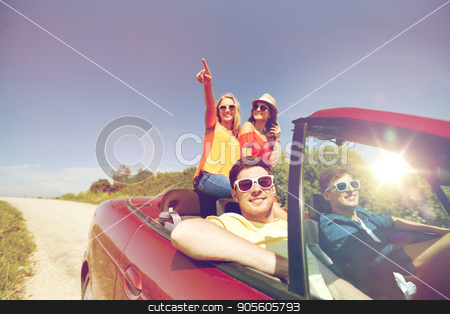 happy friends driving in cabriolet car at country stock photo, leisure, road trip, travel and people concept - happy friends driving in cabriolet car along country road and pointing finger to something by Syda Productions