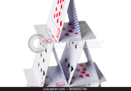 house of playing cards over white background stock photo, casino, gambling, games of chance, hazard and insecurity concept - close up of house of playing cards over white background by Syda Productions
