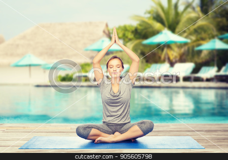 woman making yoga meditation in lotus pose on mat stock photo, fitness, sport, people and healthy lifestyle concept - woman making yoga meditation in lotus pose on mat over beach and swimming pool background by Syda Productions