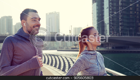 happy couple with earphones running in city stock photo, fitness, sport, people, technology and lifestyle concept - happy couple running and listening to music in earphones over dubai city street background by Syda Productions