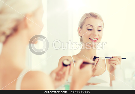 woman with makeup brush and eyeshade at bathroom stock photo, beauty, make up, cosmetics, morning and people concept - young woman applying eyeshade with makeup brush and looking to mirror at home bathroom by Syda Productions