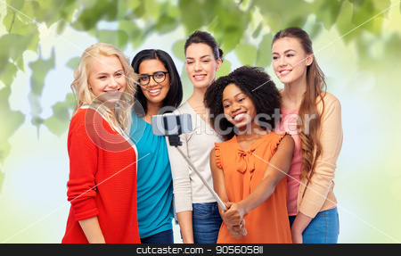 international group of happy women taking selfie stock photo, diversity, race, ethnicity, technology and people concept - international group of happy smiling different women taking picture with smartphone on selfie stick over green natural background by Syda Productions