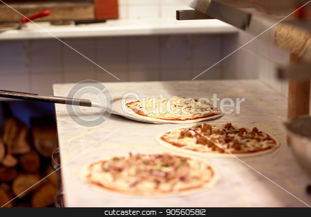 peel taking pizza off table at pizzeria stock photo, food, italian kitchen, culinary, baking and cooking concept - peel taking pizza off table at pizzeria by Syda Productions