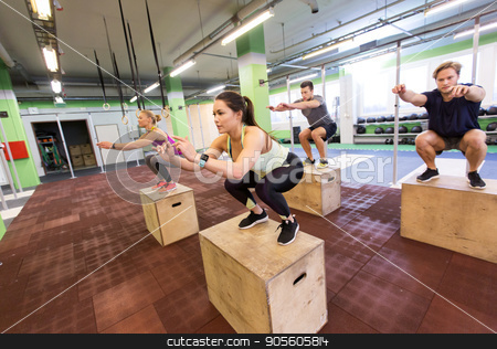 group of people doing box jumps exercise in gym stock photo, fitness, sport, training and exercising concept - group of people doing box jumps in gym by Syda Productions
