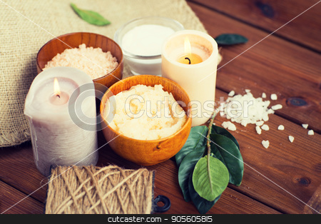 close up of natural body scrub and candles on wood stock photo, beauty, spa, therapy, natural cosmetics and wellness concept - close up of body scrub with himalayan pink salt and candles on wood by Syda Productions