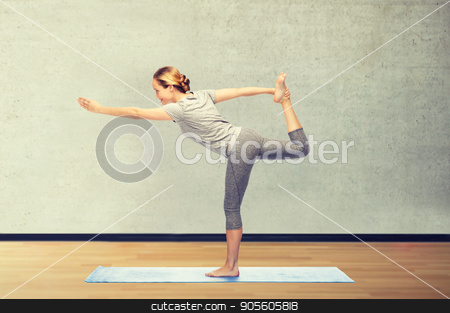 woman making yoga in lord of the dance pose on mat stock photo, fitness, sport, people and healthy lifestyle concept - woman making yoga in lord of the dance pose on mat over gym room background by Syda Productions