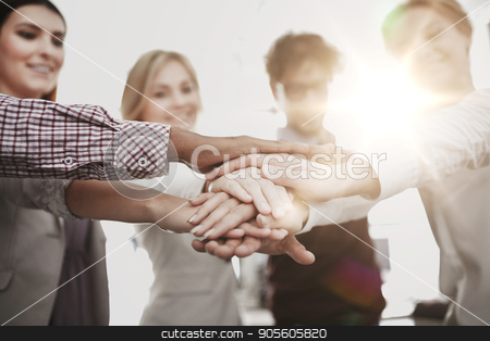 happy business team with hands on top at office stock photo, business, startup, gesture, people and teamwork concept - happy creative team with hands on top of each other at office by Syda Productions