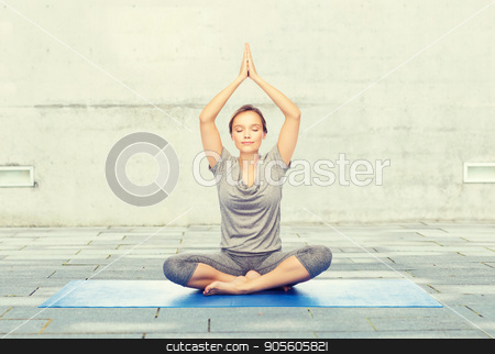 woman making yoga meditation in lotus pose on mat stock photo, fitness, sport, people and healthy lifestyle concept - woman making yoga meditation in lotus pose on mat over urban street background by Syda Productions