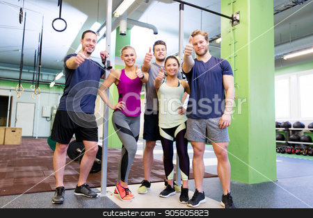 group of happy friends in gym stock photo, fitness, sport and people concept - group of happy friends in gym showing thumbs up gesture by Syda Productions