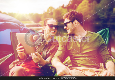 happy couple with tablet pc at camping tent stock photo, travel, hiking, technology, tourism and people concept - smiling couple with tablet pc computer sitting on chairs at camping tent by Syda Productions