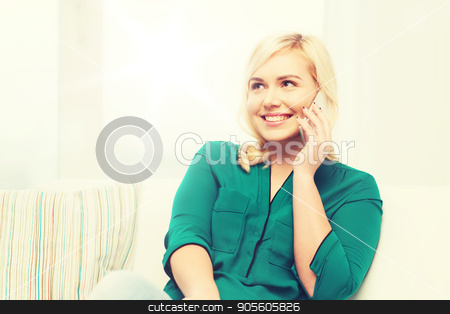 happy young woman calling on smartphone at home stock photo, people, technology, communication and leisure concept - happy young woman calling on smartphone at home by Syda Productions