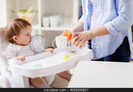baby and mother pouring juice to cup at home stock photo, family, eating, feeding and people concept - little baby and mother pouring natural carrot juice from glass bottle to cup at home kitchen by Syda Productions