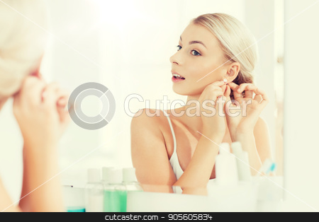 woman trying on earring looking at bathroom mirror stock photo, beauty, jewelry and people concept - smiling young woman trying on diamond earring and looking to mirror at home bathroom by Syda Productions