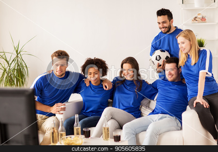 friends or football fans watching soccer at home stock photo, friendship, leisure, sport and entertainment concept - happy friends or football fans with ball watching soccer on tv at home by Syda Productions