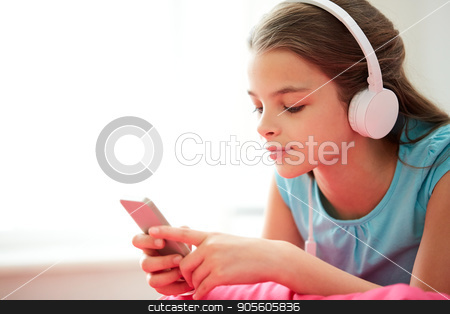 close up of girl with smartphone and headphones stock photo, children, technology and people concept - close up of happy girl with smartphone and headphones listening to music at home by Syda Productions