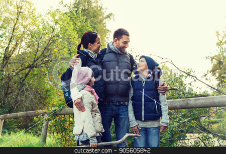 happy family with backpacks hiking stock photo, adventure, travel, tourism, hike and people concept - happy family walking with backpacks in woods by Syda Productions