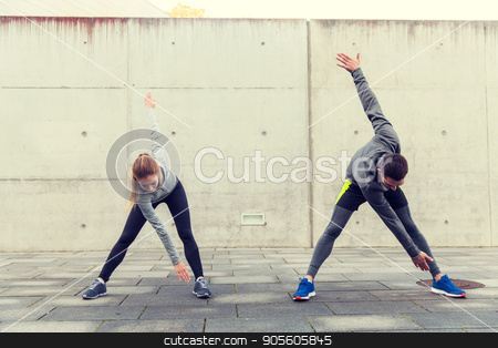 close up of couple stretching on city street stock photo, fitness, sport, exercising, training and people concept - close up of couple stretching on city street by Syda Productions