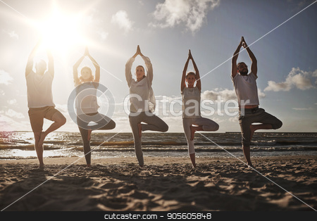 group of people making yoga in tree pose on beach stock photo, yoga, fitness, sport and healthy lifestyle concept - group of people in tree pose on beach by Syda Productions