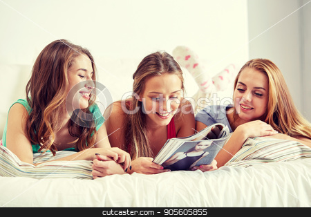 friends or teen girls reading magazine at home stock photo, friendship, people and pajama party concept - happy friends or teenage girls reading magazine in bed at home by Syda Productions