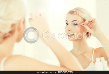 woman fixing makeup with cotton swab at bathroom stock photo, beauty, hygiene and people concept - smiling young woman fixing makeup with cotton swab and looking to mirror at home bathroom by Syda Productions