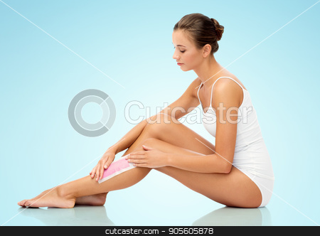 woman removing leg hair with depilatory wax strip stock photo, beauty, hair removal and people concept - beautiful woman applying depilatory wax strip to her leg skin over blue background by Syda Productions