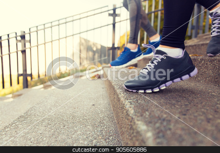 close up of feet running downstairs in city stock photo, fitness, sport, people and lifestyle concept - close up of feet in shoes running downstairs in city by Syda Productions