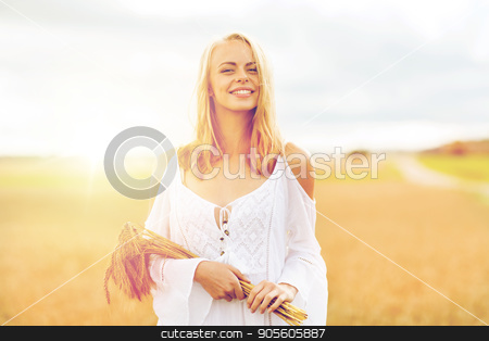 happy young woman with spikelets on cereal field stock photo, country, nature, summer holidays, vacation and people concept - smiling young woman in white dress with spikelets walking along on cereal field by Syda Productions