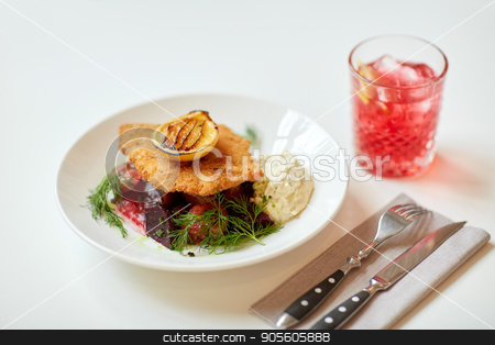 close up of fish salad with roasted lemon on plate stock photo, food, new nordic cuisine, dinner, culinary, haute cuisine and cooking concept - close up of breaded fish fillet with tartar sauce and oven-baked beetroot tomato salad on plate by Syda Productions