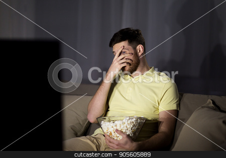scared man watching tv and eating popcorn at night stock photo, people, mass media, television and entertainment concept - scared young man watching tv and eating popcorn at night at home by Syda Productions