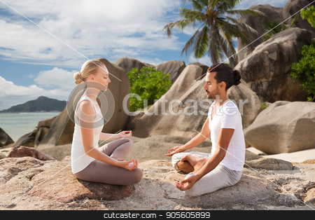 happy couple doing yoga and meditating outdoors stock photo, fitness, sport, meditation and people concept - happy couple doing yoga and meditating outdoors over tropical natural background by Syda Productions